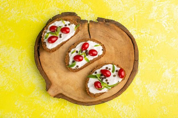 Vista dall'alto di toast di pane con panna acida e cornioli sulla superficie gialla