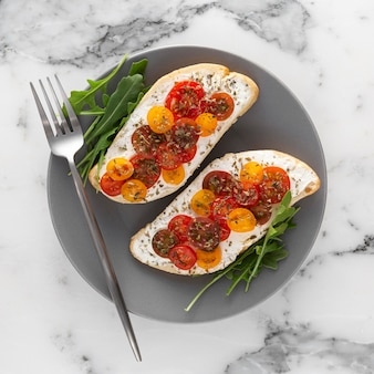 Top view bread with cream cheese and cherry tomatoes on plate with fork