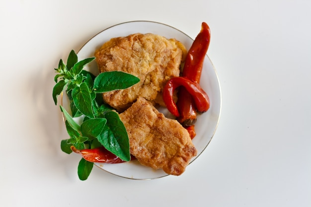 Top view of breaded chicken with chili peppers