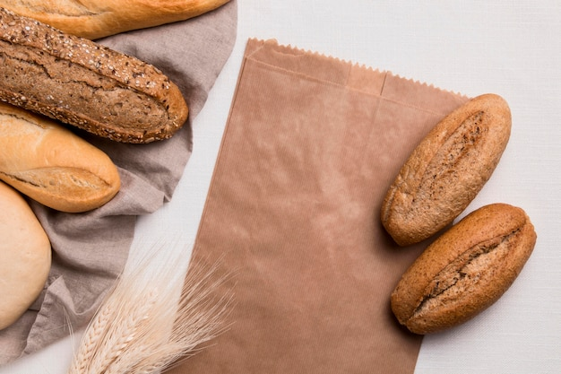 Вид сверху хлеба и бумажной упаковки с пшеницей