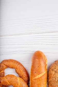 Top view of breads as bagel baguette on wooden background with copy space