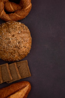 Vista superiore dei pani come baguette della pannocchia del bagel e pane nero affettato dalla parte di sinistra e fondo marrone rossiccio con lo spazio della copia