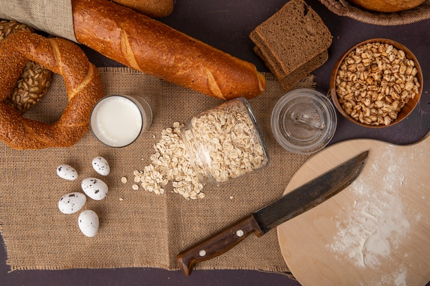 Top view of breads as bagel rye and baguette with milk oat-flakes eggs corns and knife on sackcloth on maroon background