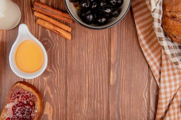 Vista dall'alto di pane come pane nero fetta di pane di segale spalmato di marmellata burro cannella olive nel latte ciotola su fondo in legno con spazio di copia
