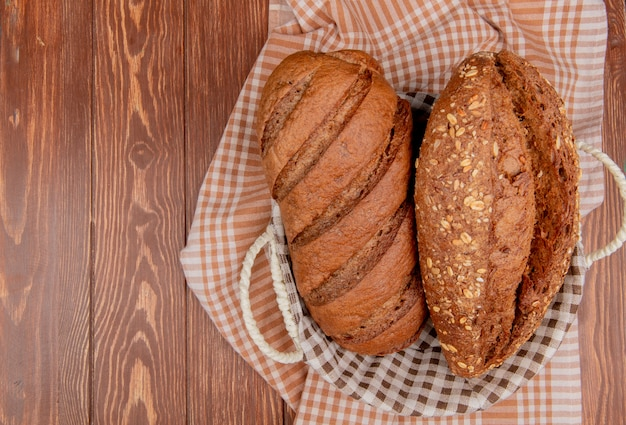 Top view of breads as black and seeded baguette in basket on plaid cloth and wooden table with copy space