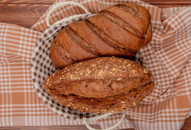 Top view of breads as black and seeded baguette in basket on plaid cloth and wooden table