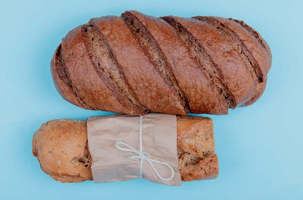 Top view of breads as crispy baguette and black bread on blue table