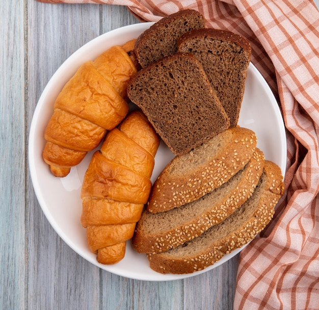 Top view of breads as croissant sliced rye and seeded brown cob in plate on plaid cloth on wooden background