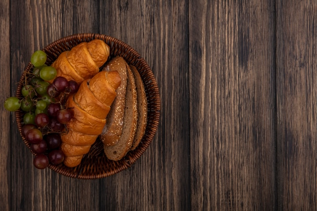 Top view of breads as croissants and seeded brown cob bread slices with grape in basket on wooden background with copy space