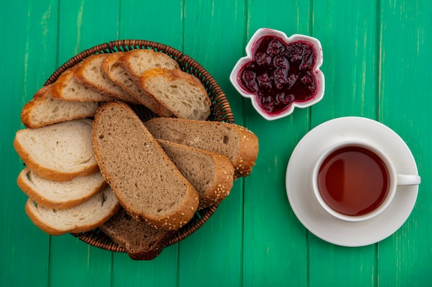 Top view of breads as seeded brown cob and baguette slices in basket and raspberry jam in bowl with cup of tea on green background