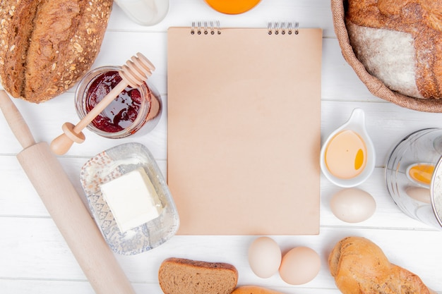 Top view of breads as seeded and vietnamese baguette rye bread cob with butters eggs strawberry jam rolling pin and note pad on wooden background with copy space