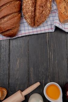 Vista dall'alto di pane come baguette vietnamite seminate e pane nero sul panno con burro mattarello latte su fondo in legno con spazio di copia
