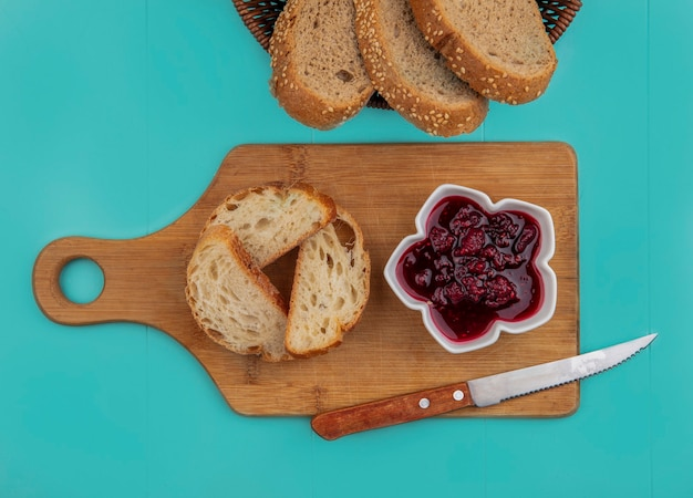 Vista dall'alto di pane come baguette a fette con semi di pannocchia marrone quelli nel cestello e sul tagliere con marmellata di lamponi e coltello su sfondo blu