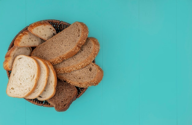 Top view of breads as sliced baguette seeded brown cob and rye ones in basket on blue background with copy space