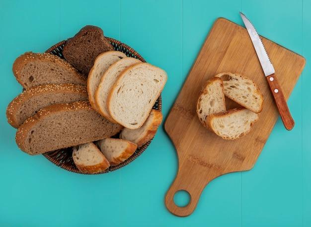 Vista dall'alto di pane come baguette a fette seminate pannocchia marrone e segale quelli nel cestello e sul tagliere con coltello su sfondo blu