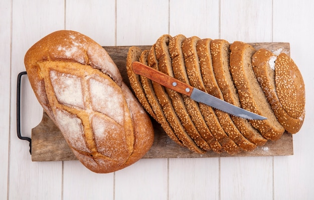 Top view of breads as sliced brown seeded cob and crusty bread with knife on cutting board on wooden background