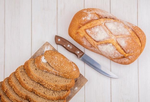 Vista dall'alto di pane come pannocchia con semi marrone a fette sul tagliere e pane croccante con coltello su sfondo di legno
