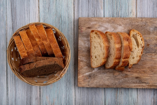 Top view of breads as sliced rye baguette and crusty ones on cutting board and in basket on wooden background