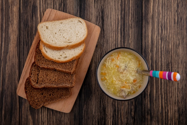 Top view of breads as sliced rye and white ones on cutting board and bowl of chicken orzo soup with spoon on wooden background