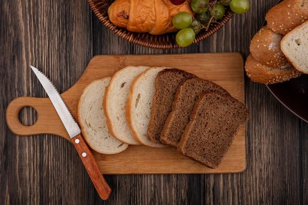 Vista dall'alto di pane come segale a fette e quelli bianchi con coltello sul tagliere e cesto di croissant uva con ciotola di semi di pannocchia marrone fette su sfondo di legno