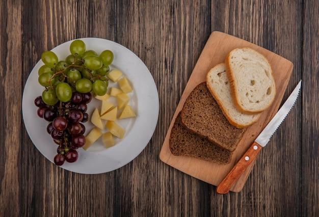 Vista dall'alto di pane come segale a fette e quelli bianchi con coltello sul tagliere e piatto di uva e formaggio su fondo di legno