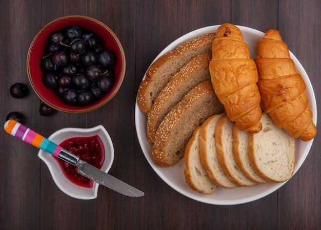 Vista dall'alto di pane come baguette di pannocchia marrone seminate a fette e croissant nel piatto e ciotole di marmellata di lamponi e prugnole con coltello su sfondo di legno