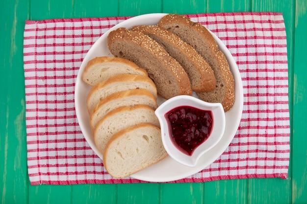 Vista dall'alto di pane come fette di pannocchia marrone seminate e baguette con una ciotola di marmellata di lamponi nella piastra su panno plaid su sfondo verde