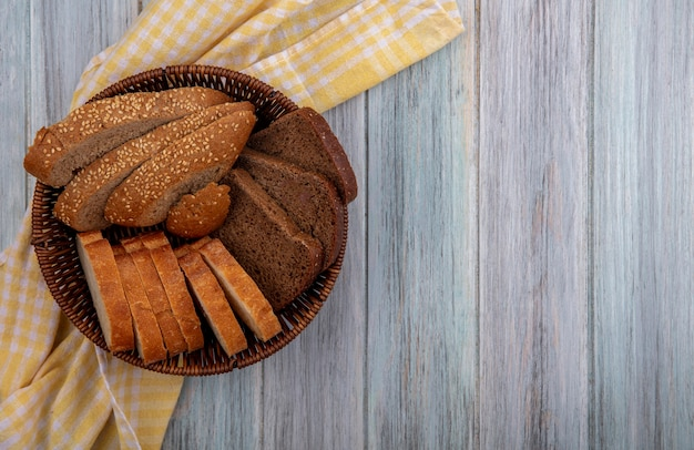 Top view of breads as sliced seeded brown cob rye and crusty ones in basket on plaid cloth on wooden background with copy space