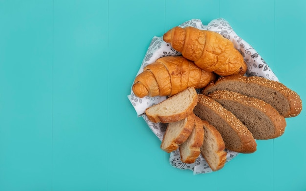 Top view of breads as sliced seeded cob baguette and croissant in bowl on blue background with copy space