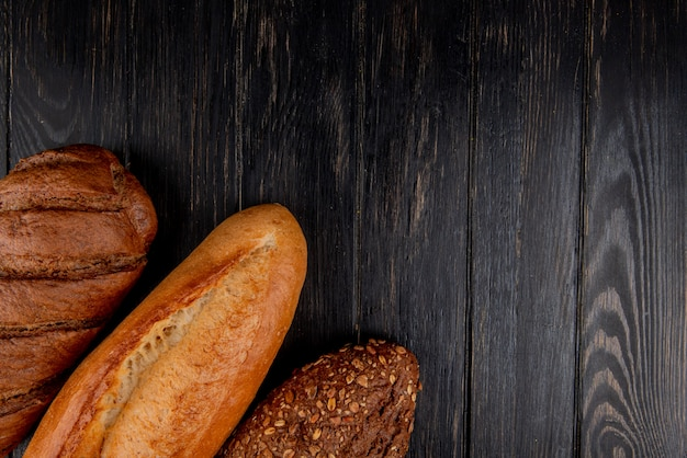 Top view of breads as vietnamese and black seeded baguette and black bread on wooden background with copy space