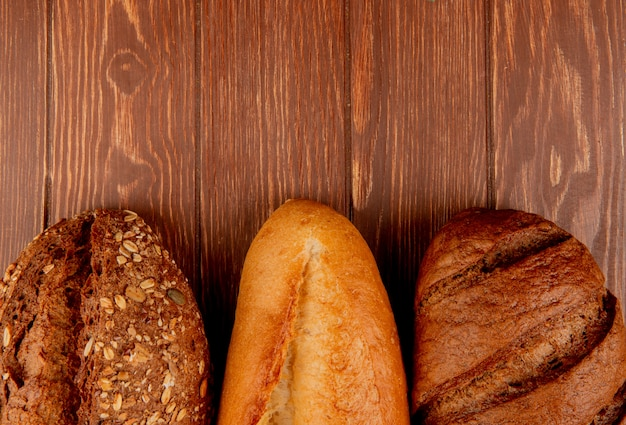 Top view of breads as vietnamese and black seeded baguette and black bread on wooden table with copy space