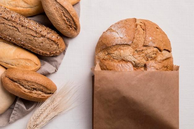Вид сверху на хлеб, смешанный с бумажной упаковкой и пшеницей