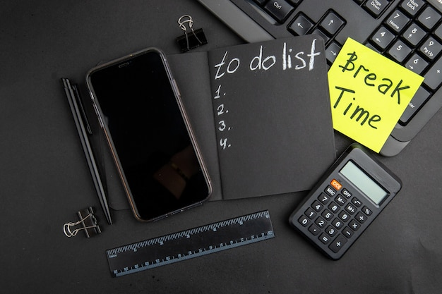 黒のメモ帳の電話ペン計算機定規バインダークリップキーボードの黒のテーブルのリストを行うために付箋に書かれた上面図の休憩時間