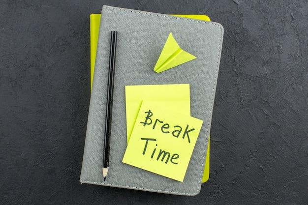 暗いテーブルのカラフルなメモ帳に黄色の付箋、黒の鉛筆で書かれた上面図の休憩時間