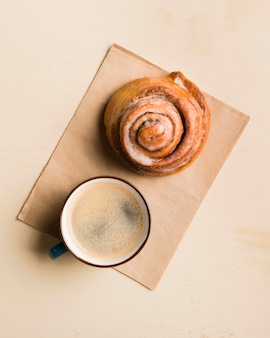 Top view breakfast arrangement with coffee and pastry