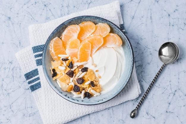 Top view breakfast bowl with orange and yogurt