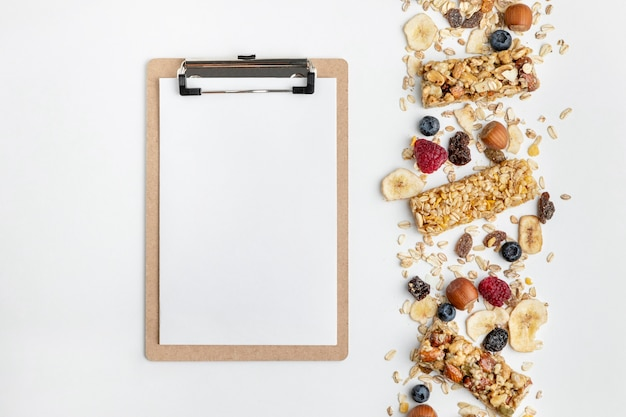 Top view of breakfast cereal bars with fruits and notepad