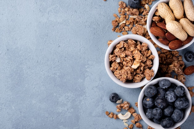 Top view of breakfast cereal in bowl with assortment of nuts and blueberries