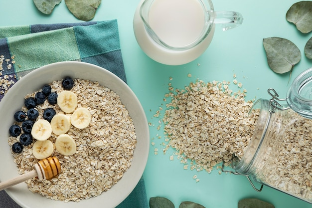 Top view of breakfast cereals in bowl with milk and fruits