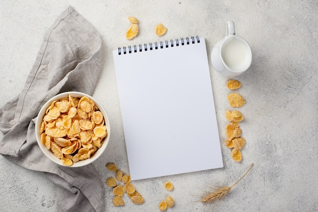 Top view of breakfast corn flakes with notebook and milk