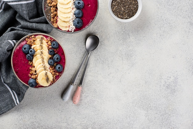 Top view of breakfast desserts in bowls with fruits and copy space