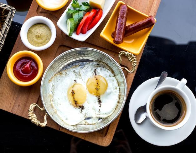 Вид сверху на завтрак жареные яйца на сковороде с колбасками и овощами с соусами и чашкой кофе