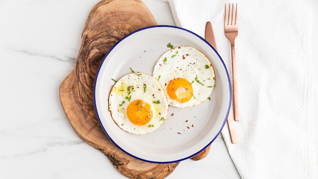 Top view of breakfast fried eggs on plate with cutlery
