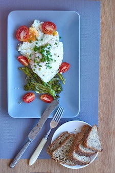 Top view breakfast, fried eggs with baked broccoli, tomatoes, whole grain bread