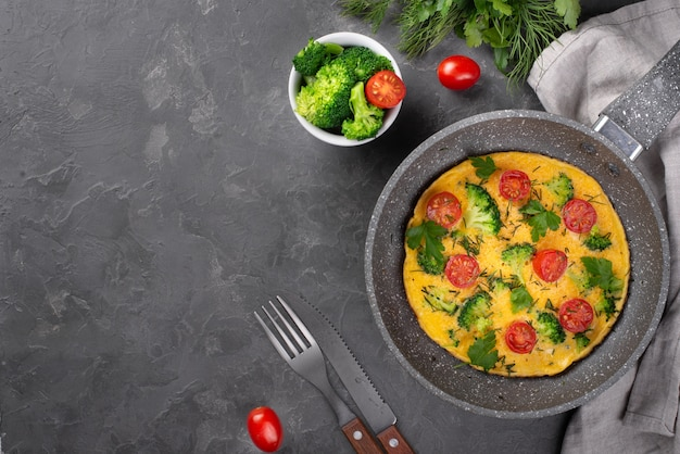 Top view of breakfast omelette in pan with tomatoes and broccoli