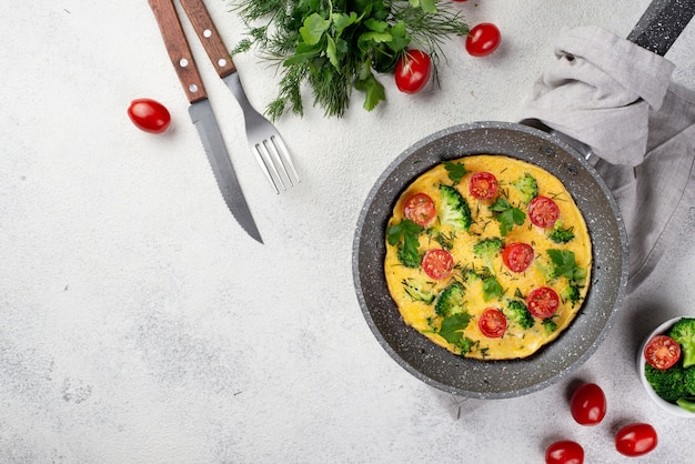 Top view of breakfast omelette in pan with tomatoes and copy space