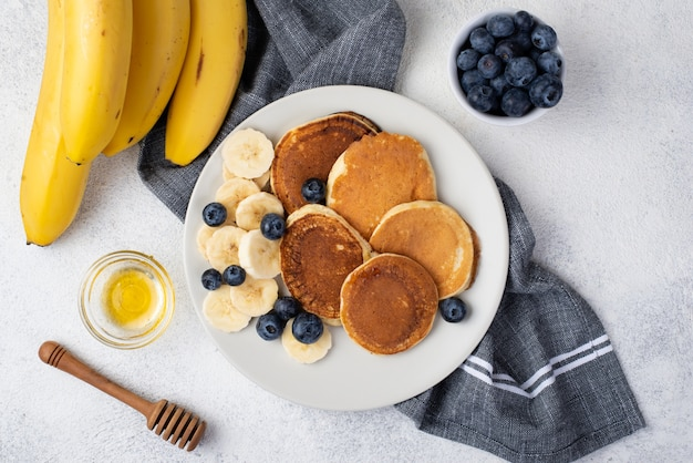 Top view of breakfast pancakes on plate with honey and bananas