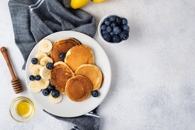 Top view of breakfast pancakes on plate with honey and blueberries