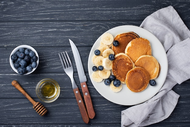 Top view of breakfast pancakes with banana slices and cutlery