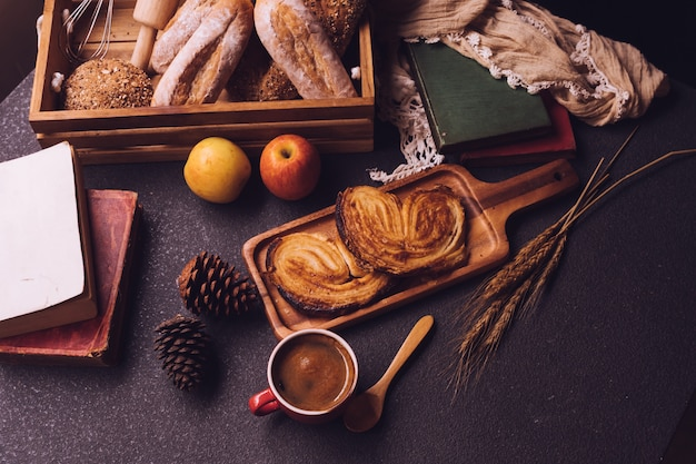 Top view of breakfast scene with coffee cup, bread and fruits on the table